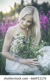 Beautiful girl in white dress sitting in meadow with wild flower bouquet in hands.