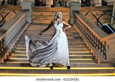 Beautiful girl in a white dress is standing on the stairs and the wind is blowing her dress