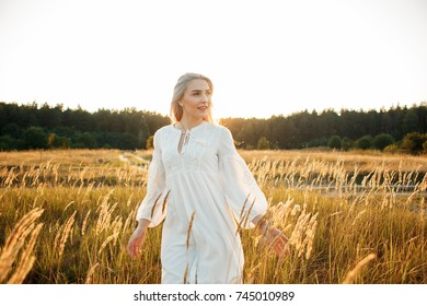 Beautiful girl in a white dress at sunset in a field. Beautiful girl is walking in nature. Portrait at sunset, yellow light, beautiful background