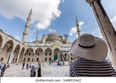 Beautiful girl in a white hat with his back to the audience at The Blue Mosque Istanbul, Turkey. Sultanahmet Camii.