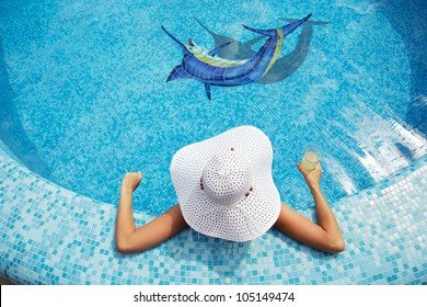 beautiful girl in white hat relaxing near a swimming pool