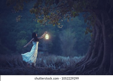 Beautiful girl in white holding a lantern in the autumn forest shining under the trees.