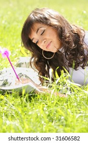 Beautiful girl in white laying down on grass and drawing