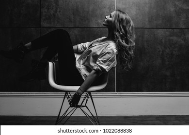 Beautiful girl in a white shirt, black jeans, glasses in an involuntary pose on a gray background. Fashion studio style full length portrait of a girl sitting on a chair