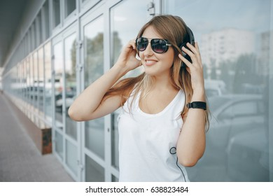 beautiful girl in a white shirt standing at the window wall with headphones