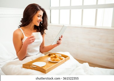 Beautiful girl in a white shirt using a tablet during breakfast in bed