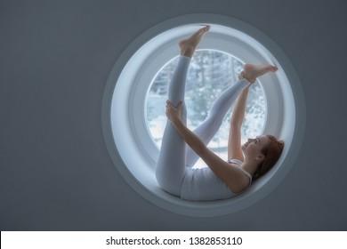 Beautiful girl in white sport wear lies on window sill in round window