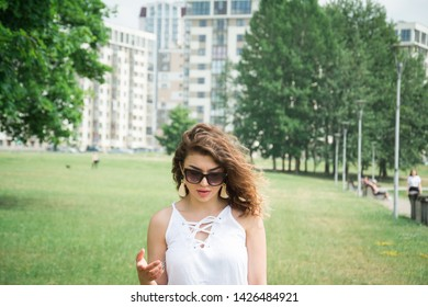 beautiful girl in a white sundress in the summer city park looks down at the green grass