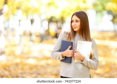A beautiful girl in a white sweater is holding a book and a tablet on the background of autumn park.