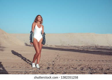 Beautiful girl in white swimsuit on sand, against backdrop of mountains of sand and blue sky. Sunbathes resting nature, jeans and sneakers. Free space for text. Emotions relaxing weekend nature.