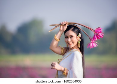 Beautiful girl in White Thai dress with red lotus flowers.Thai girl in retro Thai dress,Beautiful Thai girl in traditional dress costume