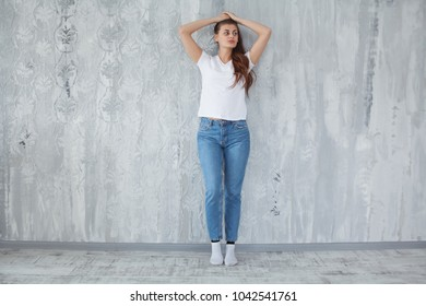 Beautiful girl in white t-shirt with long and beautiful hair on dark background, emotion. Mock-Up