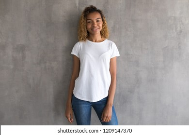 Beautiful girl in a white t-shirt on a gray background. Mock-up.