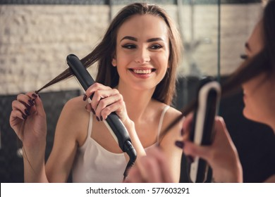 Beautiful girl in white undershirt is using a hair straightener and smiling while looking into the mirror in bathroom