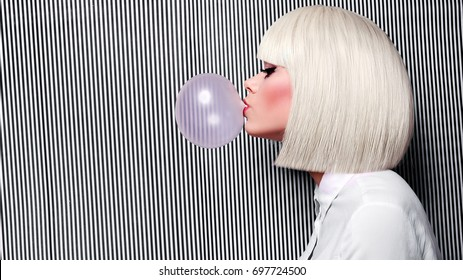 Beautiful girl in white wig blew up in pink gum bubble. A young girl in the studio on a background of a black and white vertical lines. Stylish girl wearing a white shirt.