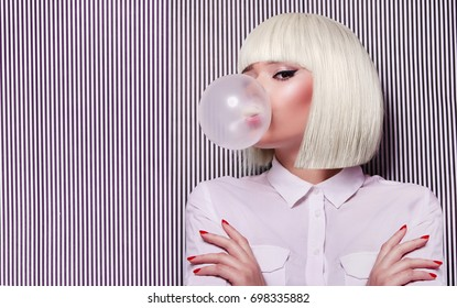 Beautiful girl in white wig blew up in pink gum bubble. A young girl in the studio on a background of a black and white vertical lines. Stylish girl wearing a white shirt.Fashion, beauty, cosmetics.