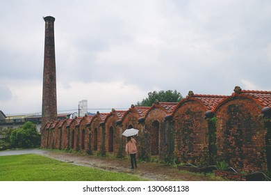 A beautiful girl who holds an umbrella is walking around in Yilan Brick Kiln. A former brick manufacturing factory in Yilan county, Taiwan.