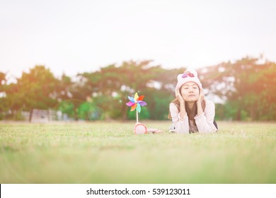 Beautiful girl with wind toy or wind turbine or pinwheel and wool hat sitting on meadow in winter season in morning.