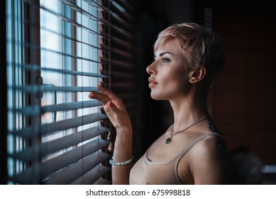 A beautiful girl at the window of the house looks out between the blinds by lifting one of them.
