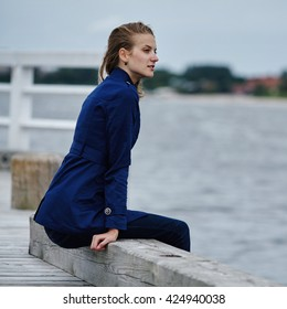 Beautiful girl with windy hair sits on pier
