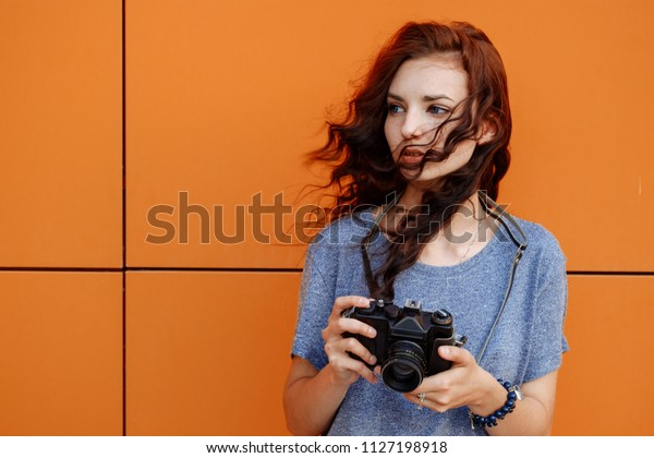 Beautiful girl with windy hair using a vintage film 35mm camera in front of orange wall with copyspace.