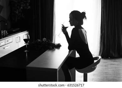Beautiful girl with wineglass.Woman alone in black dress . Black and white photo
