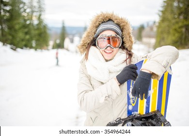 Beautiful girl in winter forest with snowboard and ski mask.Girl snowboarding in the mountains on ski  slope.Sport woman in snowy mountains.Young woman holding snowboard.Concept of winter holiday
