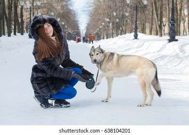 Beautiful girl in winter park walking with dog