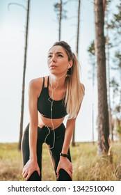 Beautiful girl woman athlete summer forest. Listening music headphones phone. Tired, resting after running shortness deep breath. Motivation for running woods. Emotion endurance strength confidence.