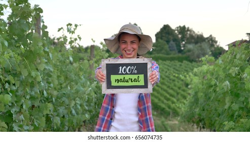 Beautiful girl (woman) farmer smiling watching the grape fields, holding a black board, in a shirt, wearing a straw hat. Concept ecology, wine bio product inspection water natural products agriculture