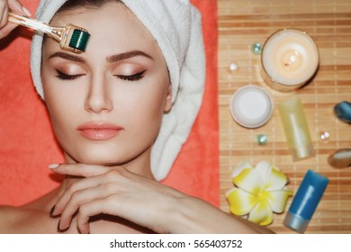 Beautiful girl woman in spa salon,facial rejuvenation procedure.Visit a beautician.Hyaluronic acid rejuvenation beauty injections mesotherapy.Concept of mesotherapy.Cosmetology.Mezoroller,mesotherapy,