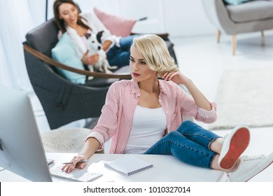 beautiful girl working with computer while her friend playing with jack russell terrier dog