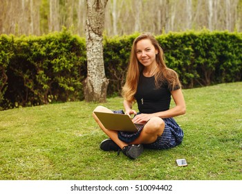 Beautiful girl working at the laptop with her phone near sitting on the grass in the park