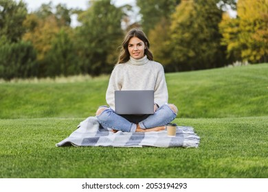 Beautiful girl working at MacBook Pro in the park