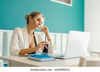 Beautiful girl working out a plan of the project and concept. Girl paints a website design on a laptop. student prints a message on the phone in the messenger. Development. Digital marketing
