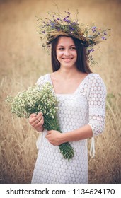 beautiful girl in a wreath from flowers with a bouquet of camomiles