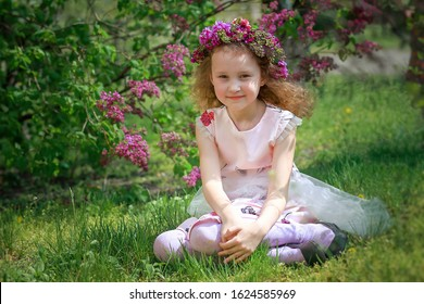 beautiful girl in wreath of lilac against background of bush with purple flowers.