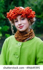 beautiful girl with a wreath on the head of rowan outdoors