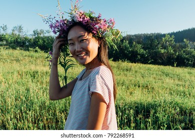 beautiful girl with a wreath on his head standing in the field