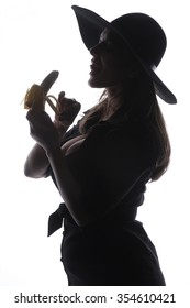 Beautiful girl and yellow banana - A beautiful brunette with gray old bowler hat on her head with a black jacket naughty kissing and licking fresh yellow raw banana - facial expressions