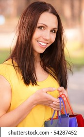 Beautiful girl in yellow clothes with purchases against summer nature.