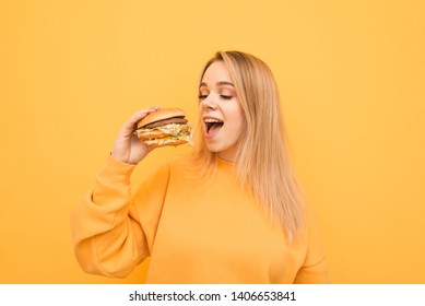 Beautiful girl in yellow clothes is standing on a yellow background with a burger in her hand and bites. Attractive girl eats fast food, holds a burger in her hand and looks hungry for fast food.
