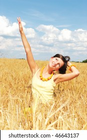 Beautiful girl in a yellow field of wheat