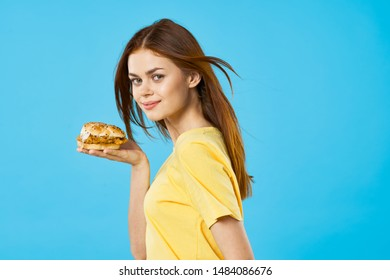 Beautiful girl in a yellow tank top with a hamburger in hand on a blue isolated background