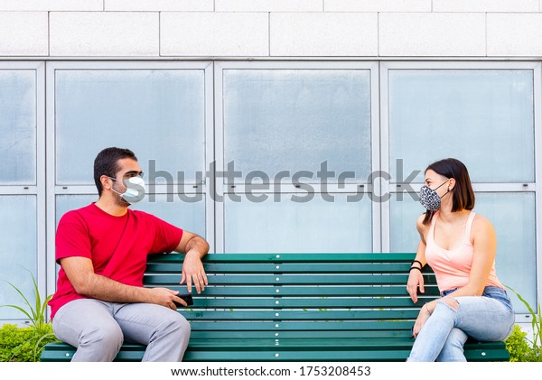 a beautiful girl and a young boy chat together observing the social distancing and wearing protective masks, the new normality with protective masks