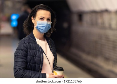 Beautiful girl, young woman standing at station in underground, metro, subway, waiting for public transport, train in medical protective mask on her face. Virus, pandemic coronavirus concept. Covid-19