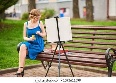 Beautiful girl-artist on the street in a blue dress, draws on the easel