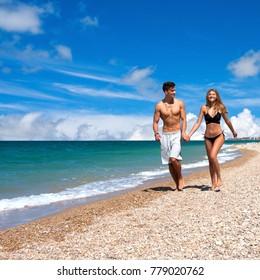 Beautiful  girlfriend and boyfriend laugh and run along the beach