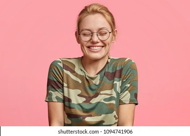 Beautiful girlfriend hears positive joke from lover, grins at camera with shut eyes, expresses positive emotions, isolated on pink background. People, emotions, facial expressions, happiness