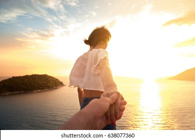 Beautiful girlfriend holding hand of her boyfriend on the beach at sunset time , Woman walking on romantic beach holding hand of boyfriend following her